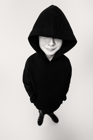 A full length portrait of a young boy in a hood. Kids, casual fashion.