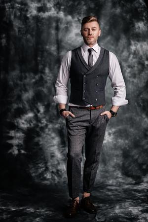Ein Porträt in voller Länge eines gutaussehenden brutalen reifen Mannes, der im Studio posiert. Lässige formelle Mode für Männer.