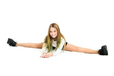 Ein Porträt in voller Länge eines lächelnden Mädchens, das sich auf dem Studioboden ausdehnt. Standard-Bild