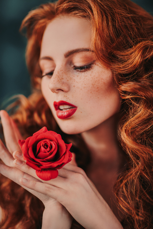 A close up portrait of a lovely mysterious girl with a red rose. Beauty, cosmetics. Stock Photo