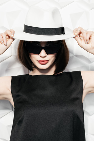 A portrait of a beautiful woman wearing a hat posing over the white background in the studio. Fashion, style, beauty.
