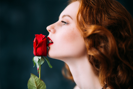 A close up portrait of a lovely mysterious girl with a red rose. Beauty, cosmetics. 写真素材