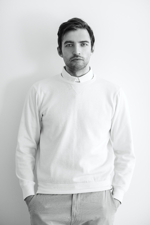 A portrait of a handsome man in white over the white background. Beauty, fashion for men.