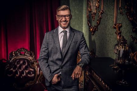 Een portret van een knappe volwassen glimlachende man in een formeel kostuum die een sigaar rookt in het klassieke interieur. Mannen schoonheid, mode.