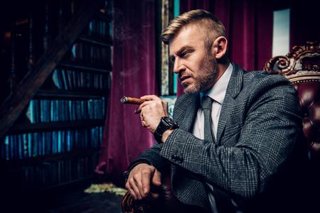 Ein Porträt eines gutaussehenden reifen Mannes in einem formellen Kostüm, der im Sessel eine Zigarre raucht. Männer Schönheit, Mode.