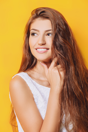 An attractive lady over a yellow background. Portrait. Natural beauty.