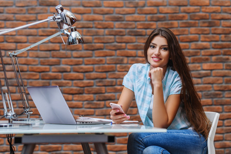 A beautiful lady sitting at a table. Office life. Work place.