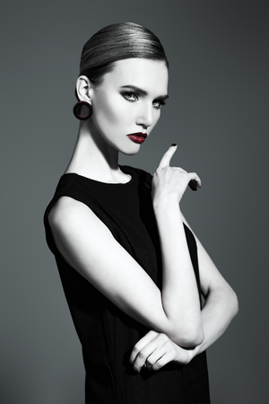 A portrait of a confident lady wearing a black dress and posing in the studio over the grey background. Beauty, make-up, style. Stock fotó