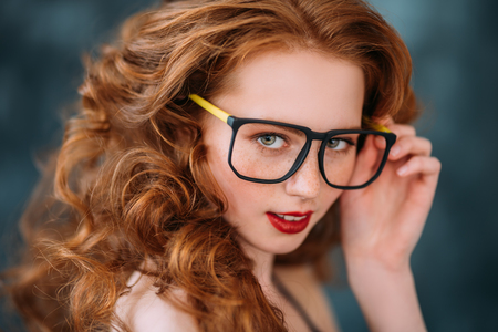 A close up portrait of a lovely beautiful girl in glasses. Beauty, cosmetics, optics.