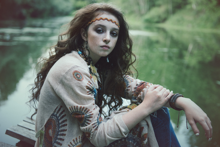 Beautiful hippie girl is sitting on the platform in the background of lake outdoor. Contemporary bohemian style. Spirit of freedom. Fashion shot. Bohemian, bo-ho style. Reklamní fotografie