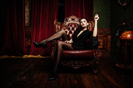 Un ritratto di una bella donna che indossa un blazer nero in posa sul divano in pelle. Moda, stile, bellezza.