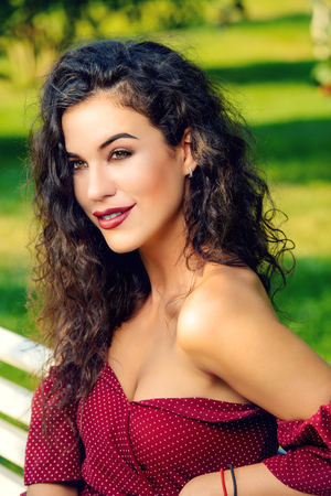 Charming woman dressed in elegant burgundy dress in a summer park. Beauty, fashion concept. Archivio Fotografico - 121767964
