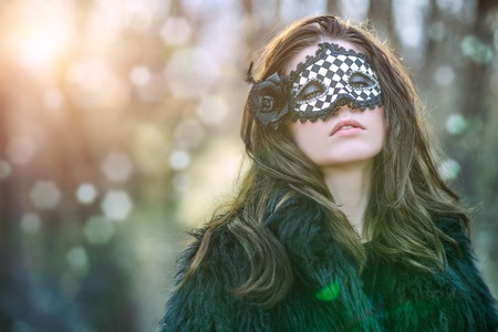 A portrait of a beautiful mysterious girl in black clothes and a mask posing in the forest. Beauty, nature.