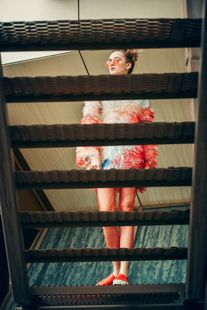 Modern young woman in fluffy dress posing behind the stairs. Beauty, street fashion.