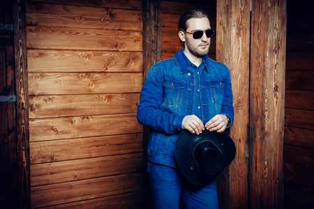 A portrait of a handsome man standing in front of the wooden house. Beauty, casual denim fashion. Reklamní fotografie