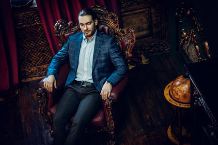 A portrait of a handsome man wearing formal clothes sitting on leather armchair in the classic interior. Men's beauty, classy fashion. Interior.