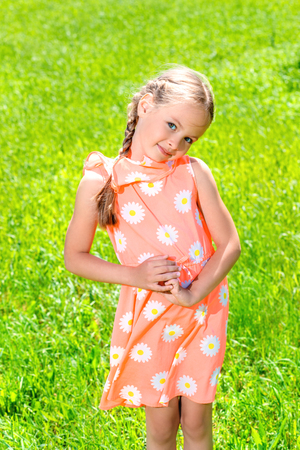 Happy little girl with pigtails in a summer park. Sunny day.