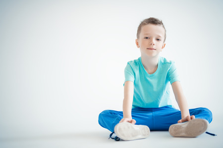 A full length portrait of a handsome child boy posing in the studio over the white background. Kids, fashion, casual style.