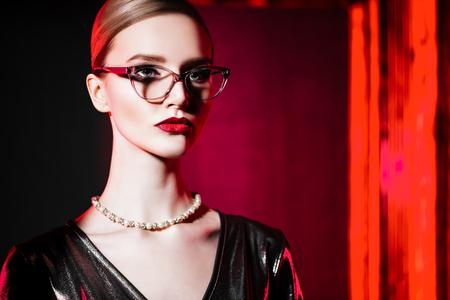 Un retrato de cerca de una dama segura con gafas. Belleza, maquillaje, estilo.