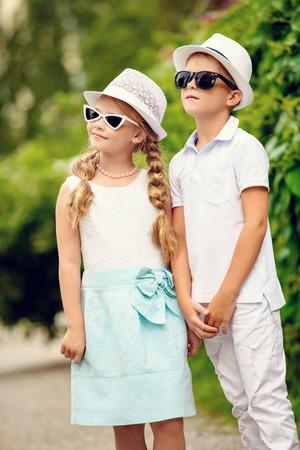 Children are walking in a park. Childhood, summer. Fashion concept. 免版税图像