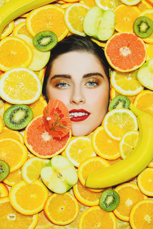 A portrait of a bright beautiful girl with a face  framing by a variety of fruit orange posing in the studio over on a background of fruit. Beauty, health.