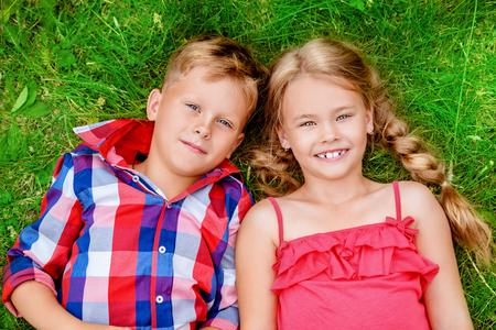 Kinderen liggen op het gras op het platteland. Mode schoonheid. Zomer.