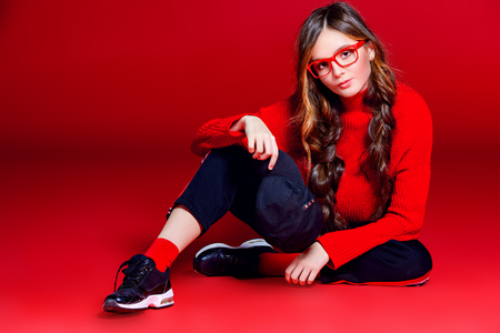 Teen style. Beautiful female model with long hair posing at studio in youth clothes. Red background. Beauty, fashion.
