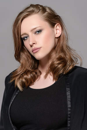 Elegant young woman wearing black fitting dress and jacket. Beauty, fashion concept. Studio shot.