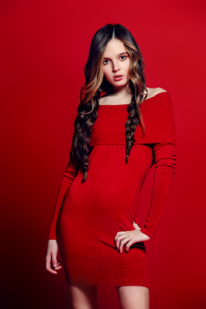 Fashion shot. Beautiful female model with long curly hair posing at studio in red dress. Red background. Beauty, fashion. Imagens