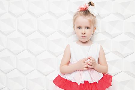 Ein Porträt eines hübschen Kindermädchens, das im Studio über dem weißen Hintergrund aufwirft. Kinder, Sommer, Schönheit. Standard-Bild