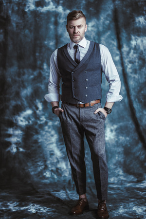 A full length portrait of a handsome brutal mature man posing in the studio. Casual formal fashion for men.