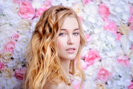 Beautiful romantic young woman with natural makeup posing on a background of roses. Perfume, cosmetics concept.