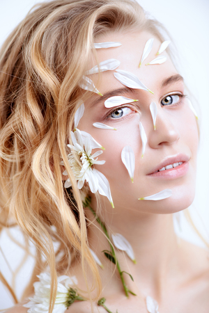 Beautiful young woman with petals of chrysanthemum on face and body. Beauty, natural cosmetics concept.