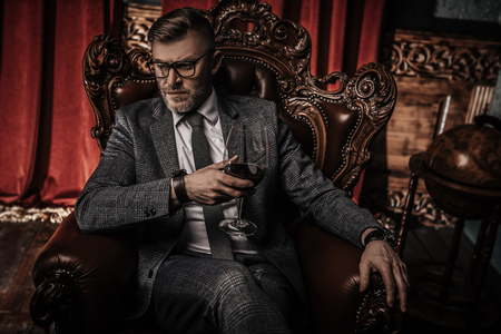Portret przystojnego dojrzałego mężczyzny w formalnym stroju pijącego wino w fotelu w klasycznym wnętrzu. Uroda męska, moda.