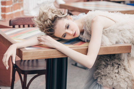 Beautiful young woman in an elegant fluffy dress posing in cafe outdoor. Beauty, street fashion.