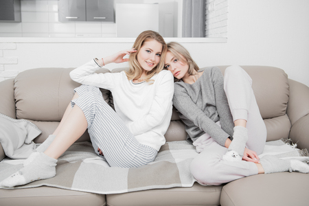 Two girlfriends are posing  in home clothes at the home. Beauty, fashion.