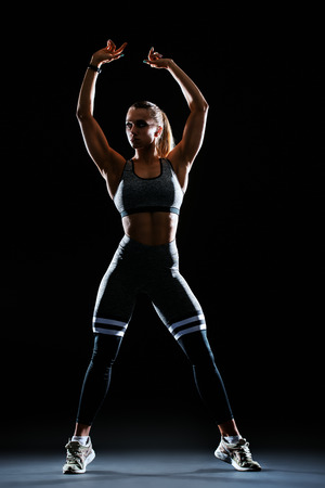 A full length portrait of a sporty young woman posing over the black background. Beauty, health, sport.