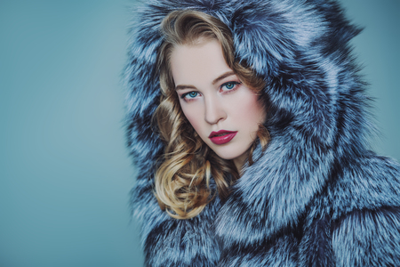 A close up portrait of a beautiful woman wearing a fur coat with hood. Beauty, winter fashion, style. Stok Fotoğraf