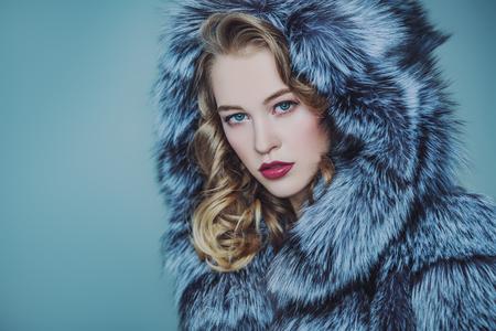 Bliska portret pięknej kobiety w futrze z kapturem. Uroda, moda zimowa, styl.
