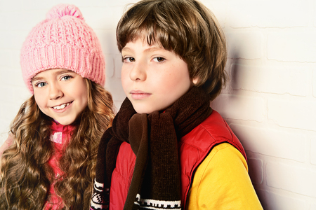 Two smiling children wearing winter clothes posing together at studio. Kid's fashion.