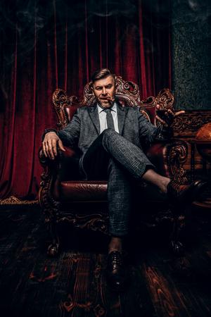 Ein Porträt in voller Länge eines gutaussehenden reifen Mannes in einem formellen Kostüm mit einem Glas Wein und einer Zigarre, die im Sessel im klassischen Interieur sitzt. Männer Schönheit, Mode.