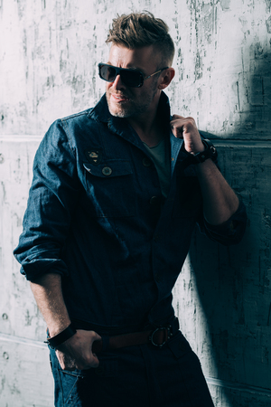 A portrait of a handsome brutal mature man posing in the studio over the grey wall. Casual denim fashion, mens beauty.
