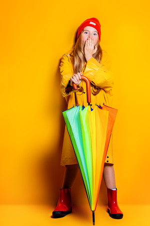 A full length portrait of a bright fashionable girl in a raincoat and a hat holding an umbrella of rainbow colors. Autumn and spring fashion for kids.