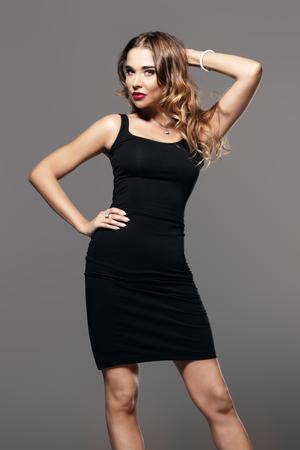 Niesamowita kobieta ubrana w elegancką czarną sukienkę i okulary przeciwsłoneczne na szarym tle. Uroda, koncepcja mody. Kolekcja sukien wieczorowych.
