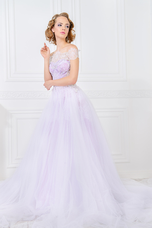 Charming bride woman in a beautiful wedding dress  with a lush skirt. Luxurious apartments. Imagens