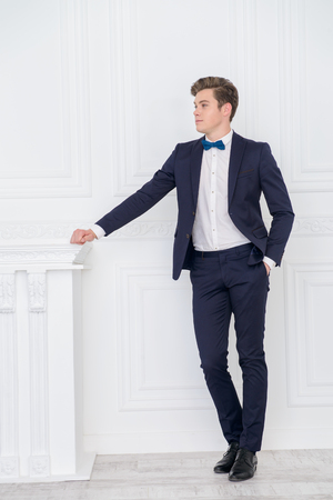 Full length portrait of a handsome young man in elegant suit posing in luxurious apartments. Male beauty, fashion.