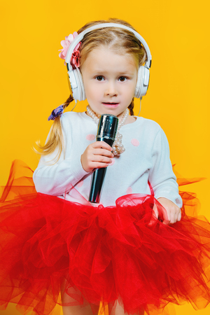 A portrait of a bright young pretty girl in skirt with a microphone. Fashion for kids. Stock Photo