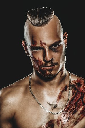Fight club, MMA. Portrait of a bad guy fighter with a face and body in the blood. Rocker, punk.