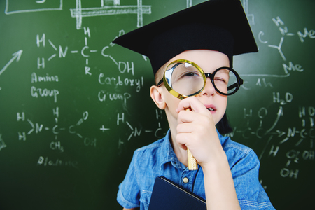 A portrait of a young boy in glasses posing  with a magnifying glass in front of the blackboard at school. Education, knowledge.