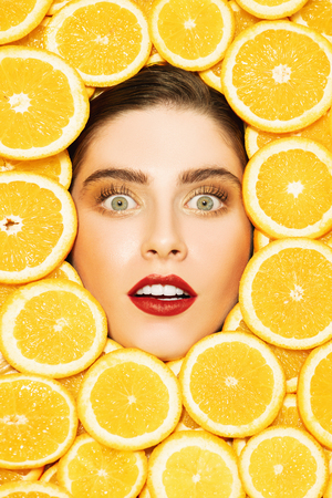 A portrait of a bright beautiful girl with juicy oranges posing in the studio over the yellow background. Beauty, health. Stock Photo